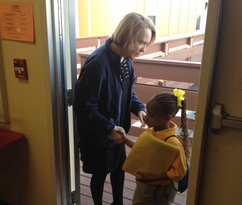 Lagniappe's principal, Kendall Petri, welcomes a student to school after checking to make sure she doesn't have an IEP.