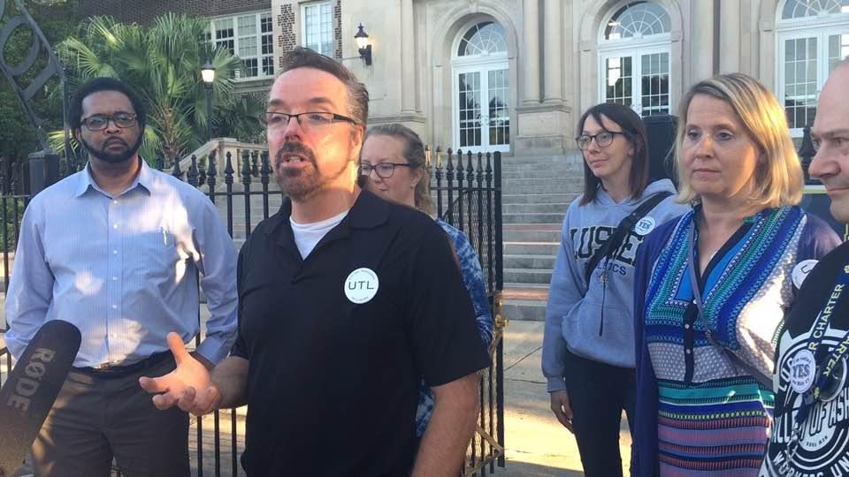 Pro-union teachers talk to reporters after losing an organizing fight in May.